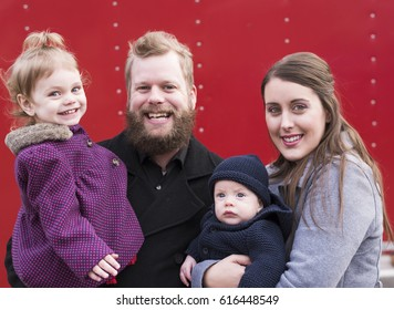 Young smiling family, including 2-year-old girl and baby boy. Family photo isolated on red pattern background, taken outdoors.