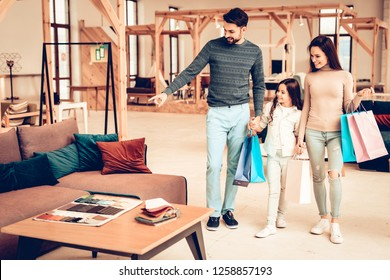 Young Smiling Family With Purchase Bags. Furniture Store Concept. Sunny Day. Good Mood. Loving Each Other. Bright Light. Happy Together. Going Shopping. Look At The Couch. Different Colors.