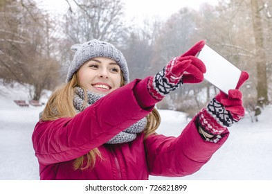 young smiling fashion woman in winter clothes holding smart phone in the background of snow.