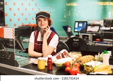 Young smiling female cashier in uniform dreamily looking in camera with products on cash line near working in modern supermarket