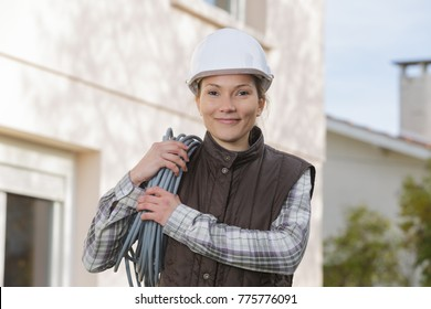 young smiling female electrician outdoors