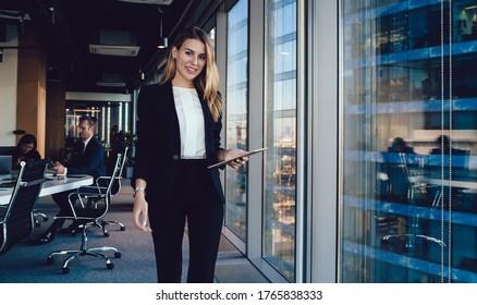Junge, lächelnde Unternehmerin in eleganten Kleiderblättertabletten während sie auf einem modernen Arbeitsplatz auf dem Hintergrund einer Gruppe beschäftigter Kollegen steht und sich die Kamera ansieht
