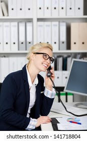 Young smiling female executive on the phone in office