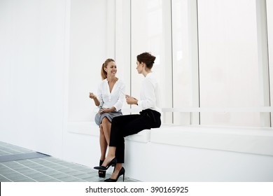 Young smiling female manager is listening story of her partner, while they are sitting in modern office interior. Cheerful happy businesswoman is talking with secretary before conference with workers