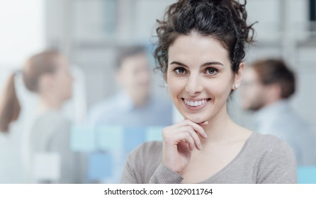 Young smiling female office worker posing, she is smiling at camera, business people on the background, job and career concept