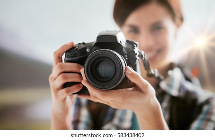 Young smiling female photographer shooting outdoors in nature, she is hiking on the mountains and holding a digital camera