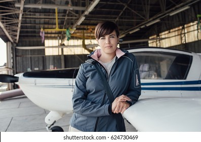 Young smiling female pilot posing in the airport hangar, she is leaning on a small aircraft wing