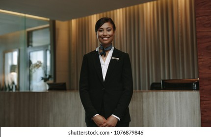 Young smiling female receptionist at the hotel front desk ready to greet guest. Female concierge looking at camera and smiling.