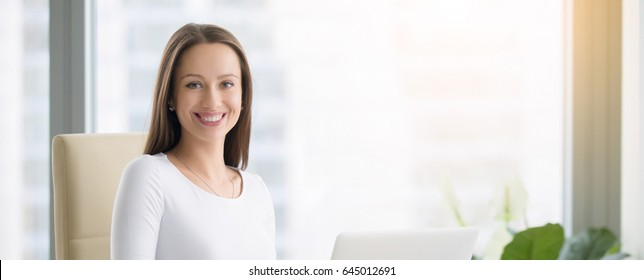 Young smiling female receptionist at the modern office desk with a laptop ready to greet clients. Looking at the camera. Horizontal photo banner for website header design with copy space for text