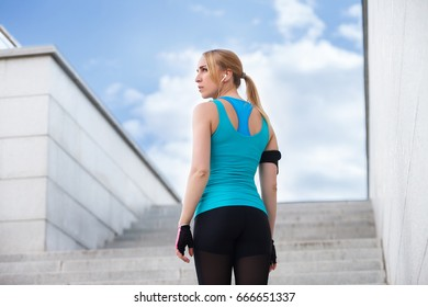 Young smiling female resting after an active fitness training standing against city stairs outdoor with copy space on right area