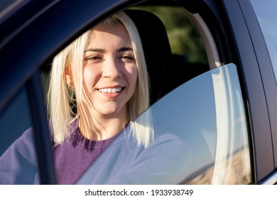 Young smiling female steering car at sunset