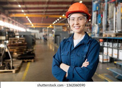 Young smiling female technician in blue uniform, protective eyeglasses and helmet working in modern factory