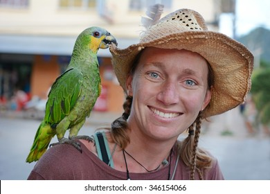 Young smiling female traveler with green parrot, Amazonia, Bolivia