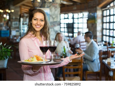 Young smiling female waiter serving restaurant guests