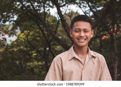 A young smiling Filipino man at the park. Dark complexion and wearing a light brown polo shirt.