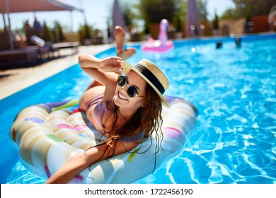 Young smiling fitted girl in bikini, straw hat relax on inflatable swan in swimming pool. Attractive woman in swimwear lies in the sun on tropical vacation. Pretty female sunbathing at luxury resort.
