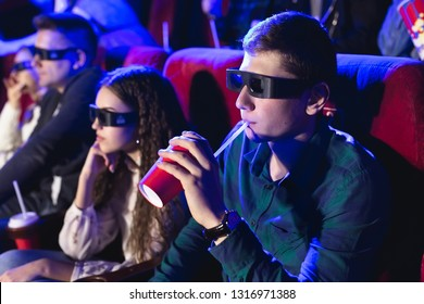 young smiling friends in 3d glasses eating popcorn and watching movie in cinema