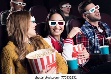young smiling friends in 3d glasses with popcorn watching movie in cinema