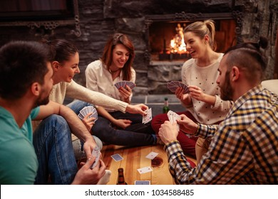 Young smiling friends partying together and playing cards