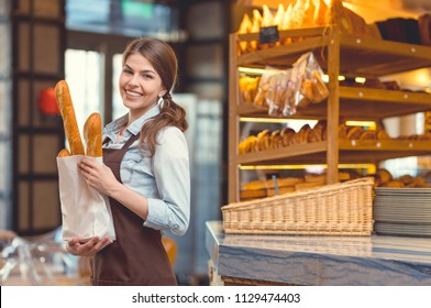 Young smiling girl with baguettes in the bakery