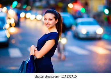Young smiling girl in blue dress standing on an evening street with bags in her hands