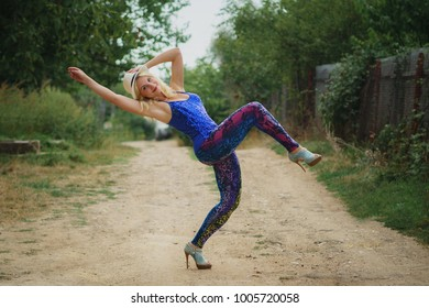 young smiling girl in colored leggings, blue top, white hat and on high heels dancing on the dirt road