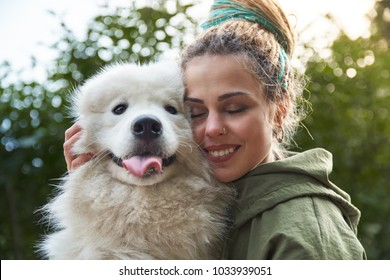 Young smiling girl with colorful dreads with a satisfied happy expression he closed his eyes and hugs his beloved dog, a Samoyed who is looking at the camera with his tongue hanging out