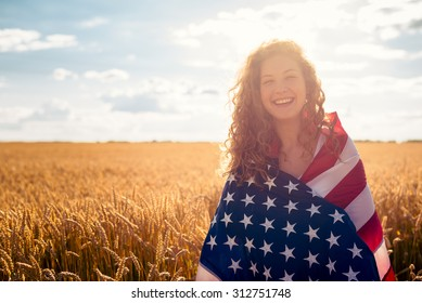 Young smiling girl covered with USA flag in golden wheat field. Selective focus. Lens flare.