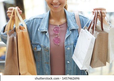 Young smiling girl in denim jacket showing various paper shopping bags full of new clothes