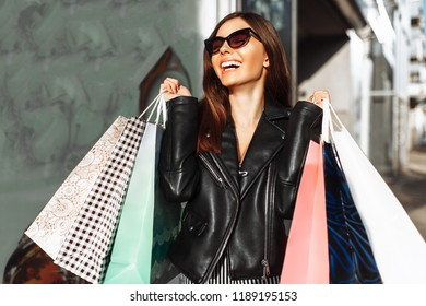A young smiling girl enjoys a successful shopping, walking down the street with bags in her hands