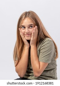 Young smiling girl looks to the side with sly and surprised expression