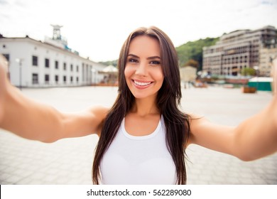Young smiling girl making selfie on the background of the city