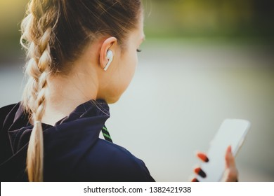 Young smiling girl making sport and running in the park using her phone to listen the music with wireless headphones on sunset in the city watching the screen