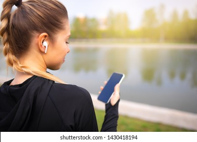 Young smiling girl making sport fitness workout and running in the park using her phone to listen the music with wireless headphones on sunset in the city watching the screen