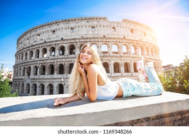 Young smiling girl on holiday in Rome with the Colosseum in the background. The blonde woman is resting on a white wall and is enjoying her vacation.