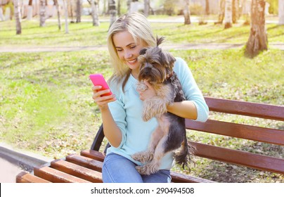 Young smiling girl owner holding phone with yorkshire terrier dog sitting in park