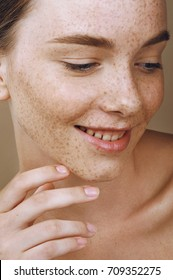 Young smiling girl with perfect skin and freckles touching her face