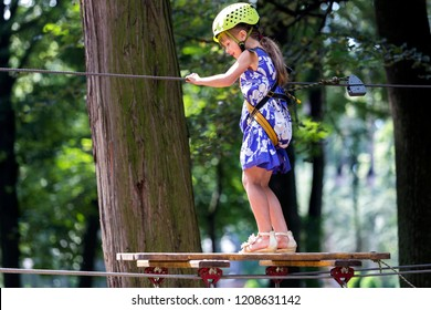 Young smiling girl in safety harness and helmet attached with carbine to cable moves carefully along rope way in recreation park on green foliage sunny bokeh background. Sport, game and leisure.