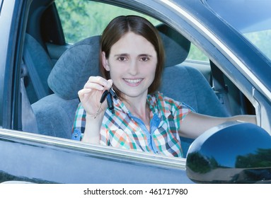 Young smiling girl sitting behind the wheel of a car and holding key in his hand.toned