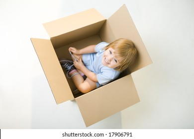 Young smiling girl sitting in cardboard box. She's looking at camera. High angle view.