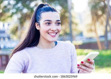 Young smiling girl sitting in the park using her mobile phone