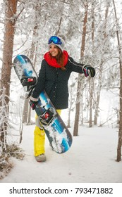 young smiling girl snowboarder going through in the fog winter forest