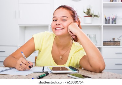 Young smiling girl student sitting and studying indoors