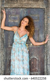 Young smiling girl in summer dress posing in front of the old wooden Arabic door