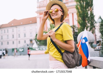 Young smiling girl in sunglasses with slovenian flag on central square of Ljubljana. Woman tourist and slovenian flag on background of city architecture. Travel, living, study in Slovenia, Europe.