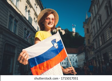 Young smiling girl in sunglasses with slovenian flag on central square of Ljubljana. Woman tourist holding slovenian flag on background of city architecture. Travel, living, study in Slovenia, Europe.
