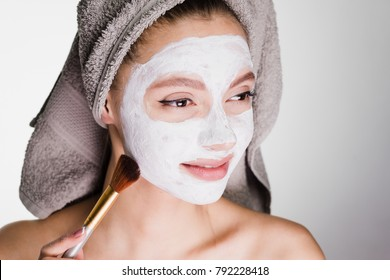young smiling girl with a towel on her head makes a spa treatment, puts on a face a white moisturizing mask with a brush