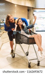 Young smiling guy with beautiful girl inside shopping trolley taking photos together on frontal camera of cellphone in modern supermarket