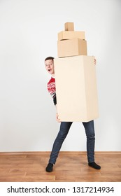 Young smiling guy with bunch of boxes on neutral background. Concept delivery, courier, moving.