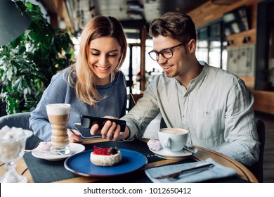 Young smiling guy and girl in headphones, watching a movie on mobile phone while sitting at cafe and drinking coffee.
